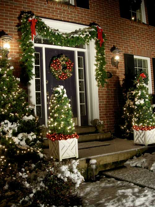 snow covered home decorated with christmas decorations and garland