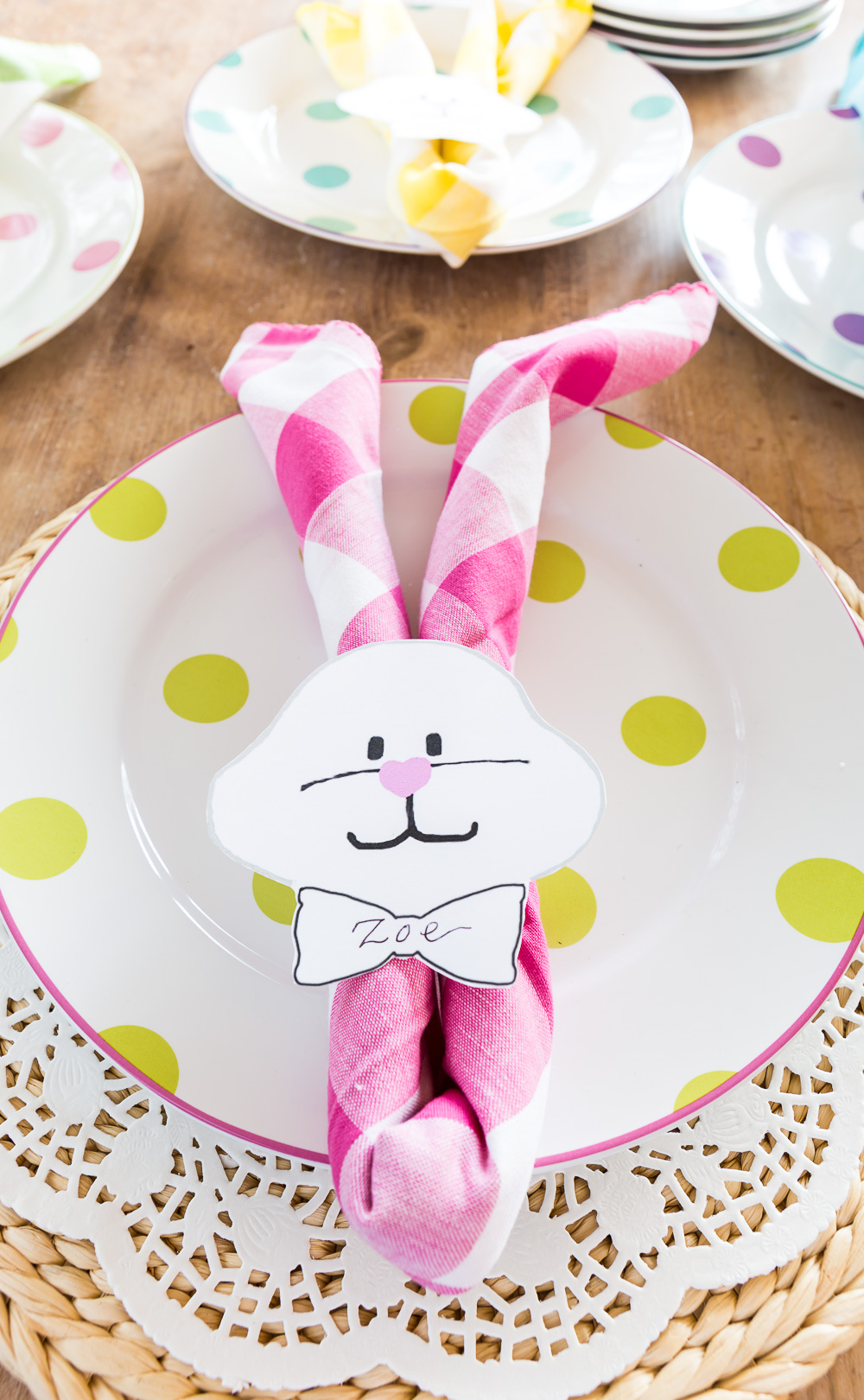 Pastel Pink Buffalo Check Napkin folded to make an Easter bunny napkin holder on a plate.