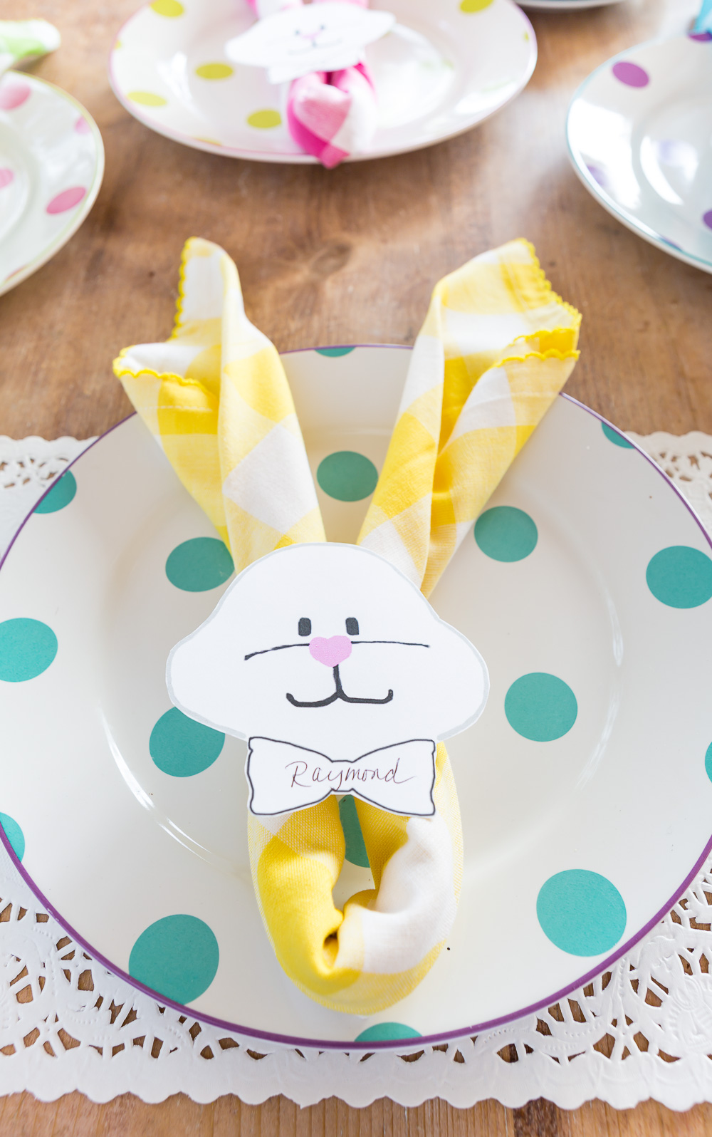Yellow and white Bunny place card on turquoise polka dot dinner plate.