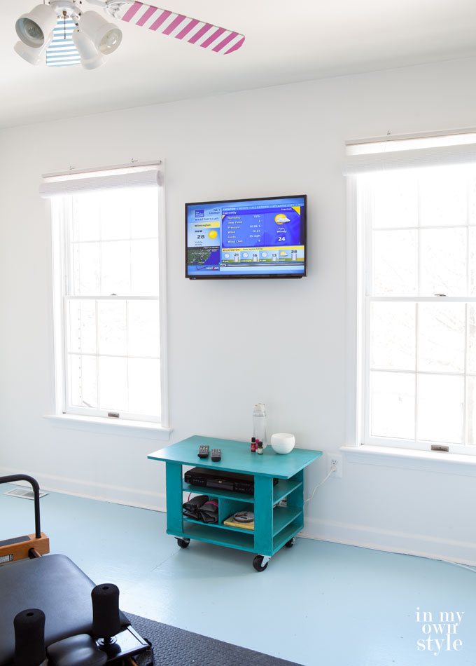 A mounted-flat-screen-TV-on-a-wall in a fitness room