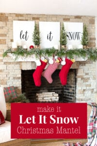 A white mantel on a stone fireplace decorated with white signs that say Let it Snow