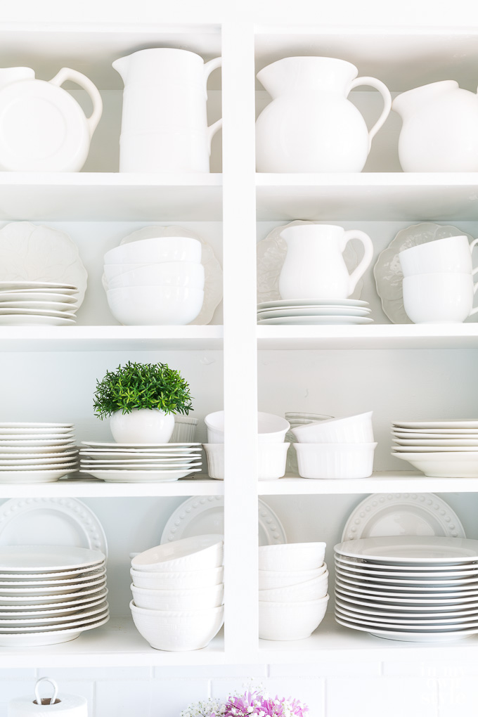 White collection of dishes - plates, cups, saucers, bowels and pitchers on white open shelving in kitchen.