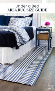 Blue and white decorated bedroom with blue and white striped area rug under the bed.