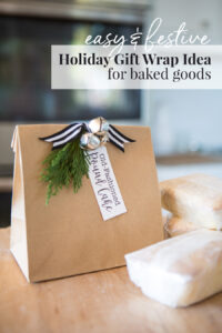 holiday baked goods placed in a brown paper bag with jingle bells to give as a hostess gift.