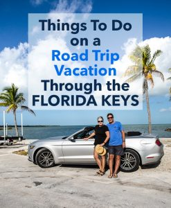 Two people standing next to convertible car on Highway 1 in the Florida Keys