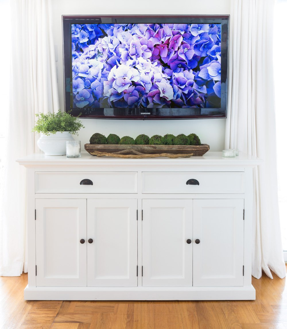 White farmhouse furniture below a wall mounted TV