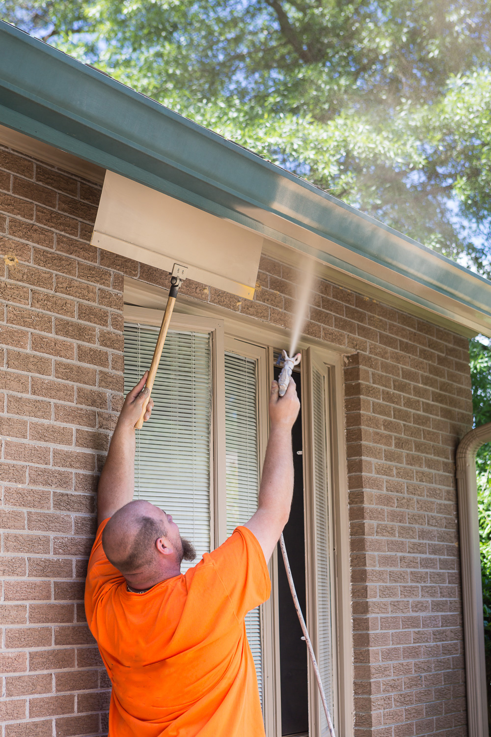 Using a paint shield to spray paint on the exterior of a home