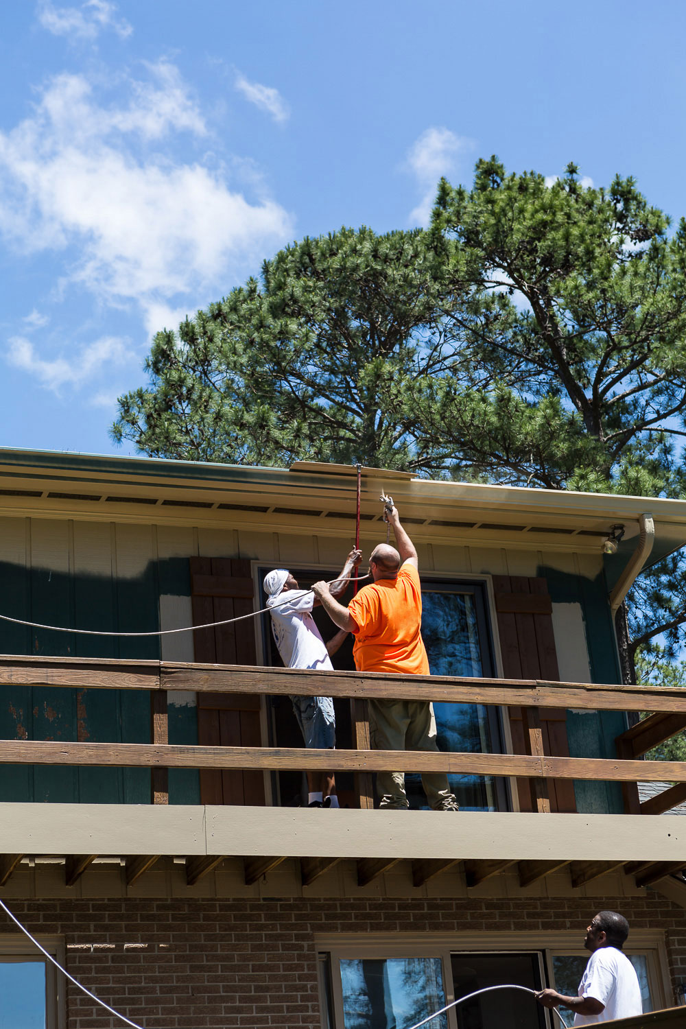 3 Painter's using a spray gun to paint the exterior of a home