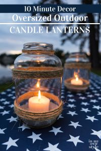 Image of picnic table with a patriotic tablecloth and DIY oversized glass candle lantern to make