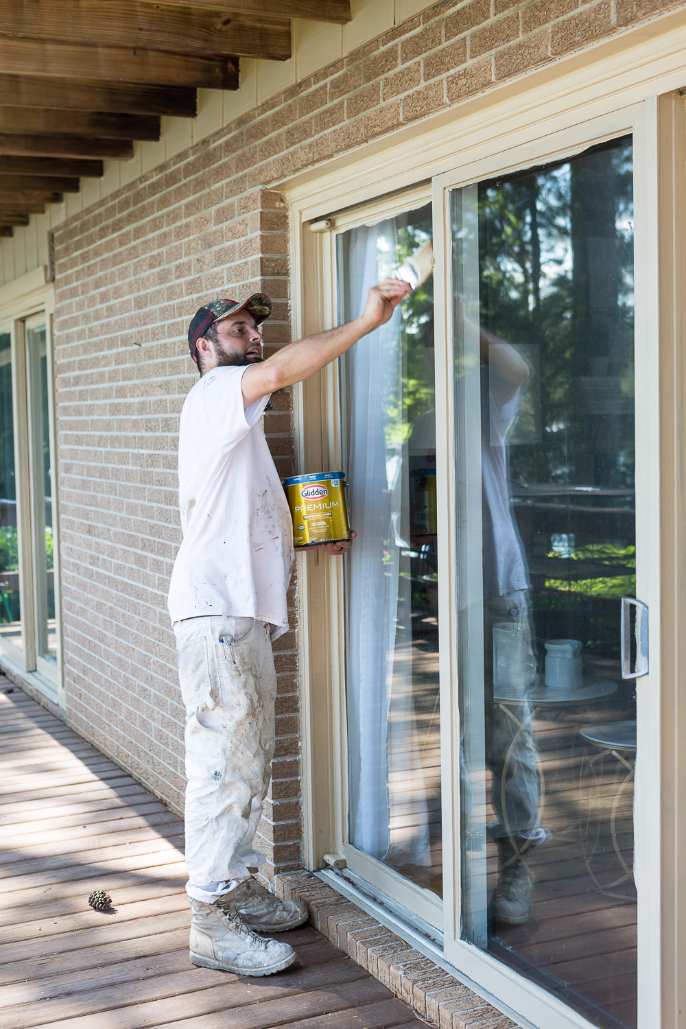Painter painting trim with Glidden Premium paint and primer in one