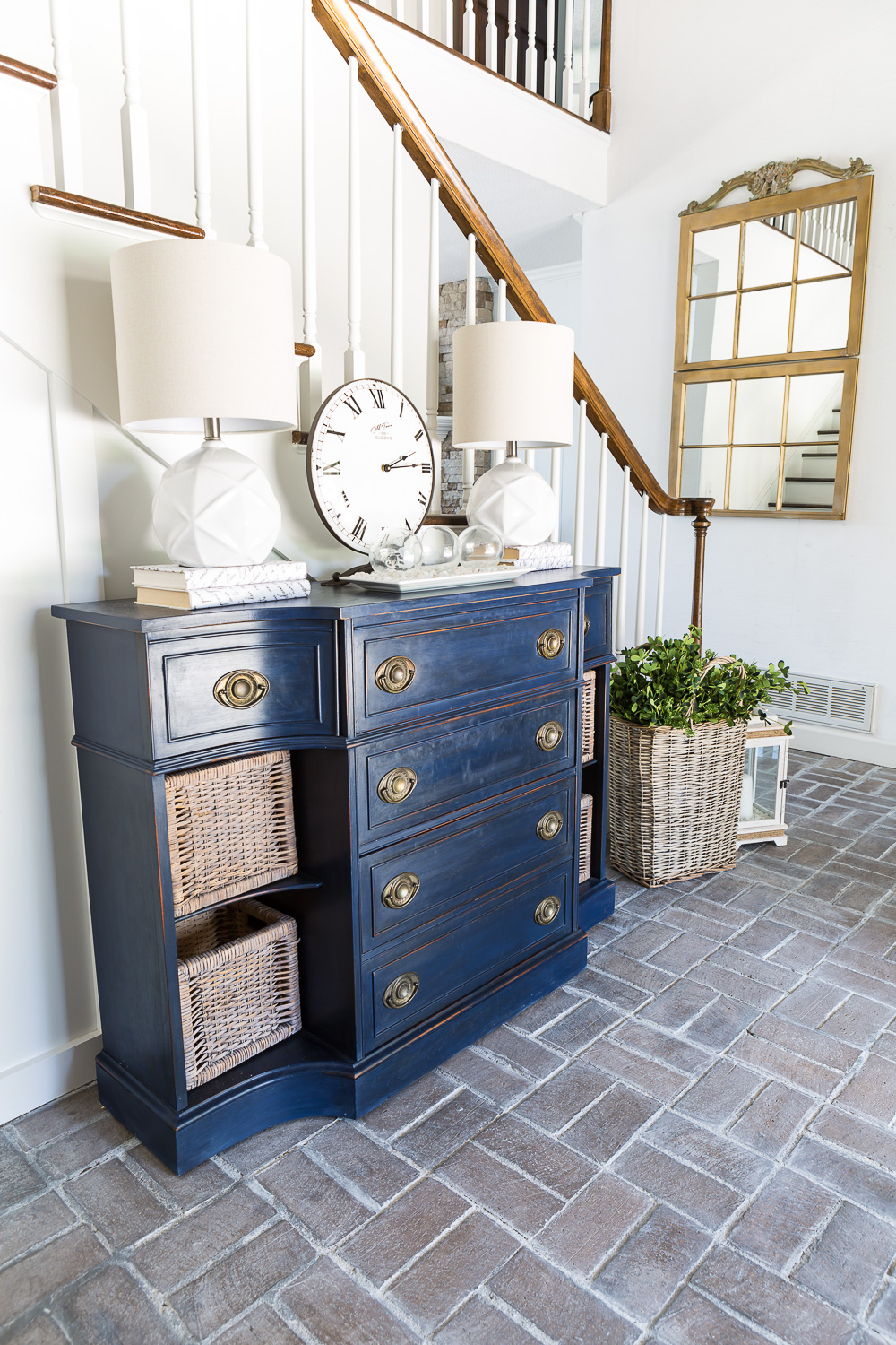 Entryway with whitewashed brick floor and navy blue chalk painted sideboard