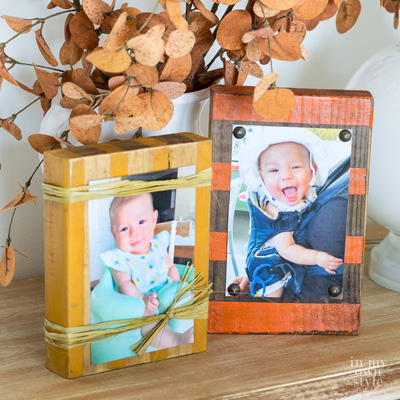 Two fall decorated wood block photo holders on a table