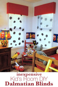 Two windows in a kid's room that have white mini blinds with Dalmatian spots.