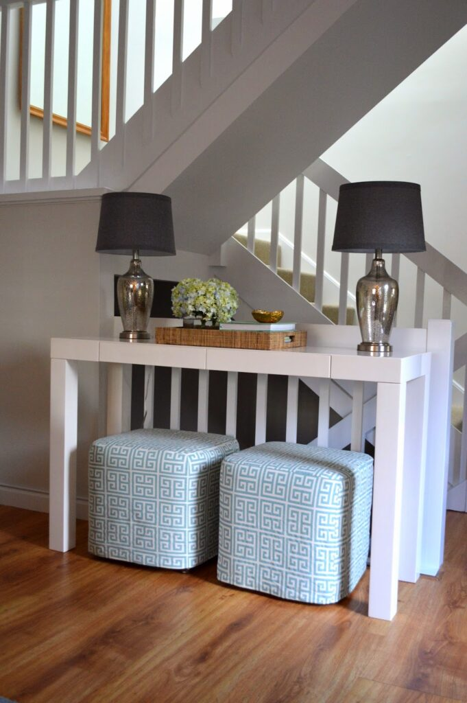 Decorating with ottomans under a foyer console table.