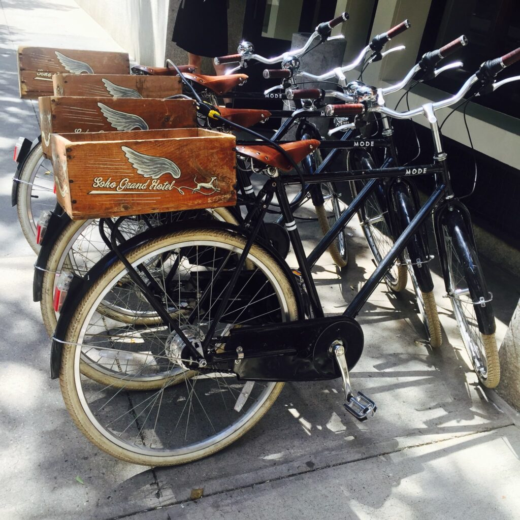 Rack on street filled with black bicycles.