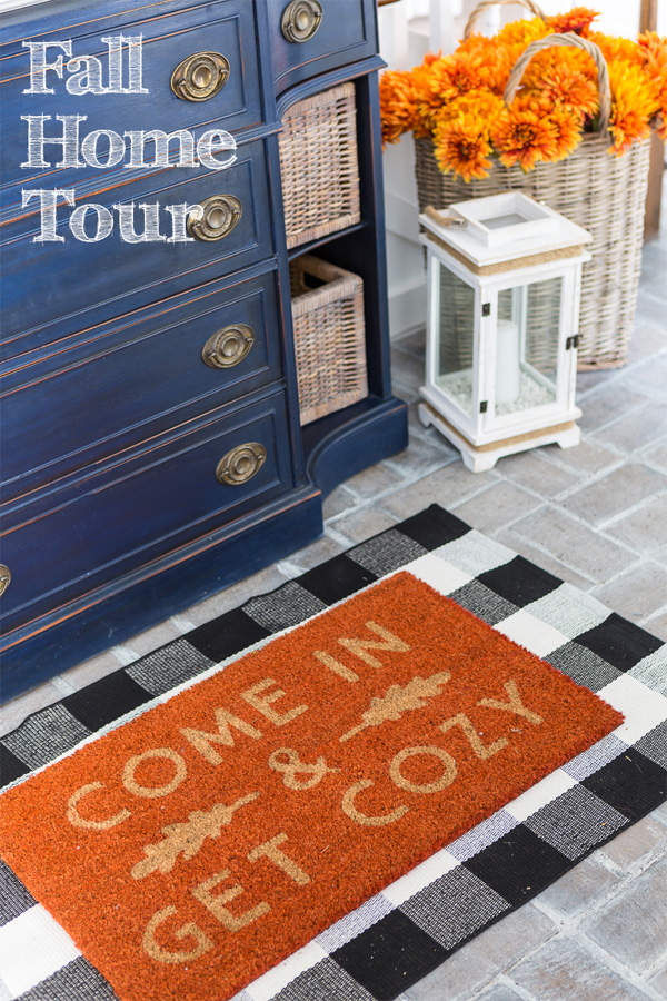 Blue sideboard in a home's entry foyer with fall door mat in front of it that says, come in and get cozy.