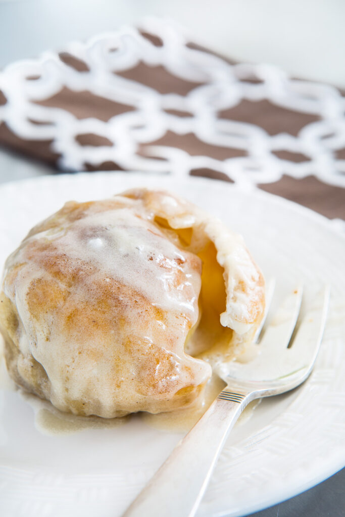 a baked apple wrapped in piecrust on a plate ready to be eaten