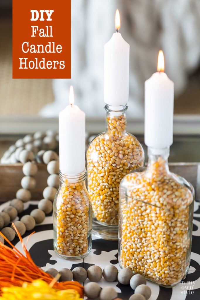 3 DIY Fall candle holders made with bottles and popcorn on a coffee table.