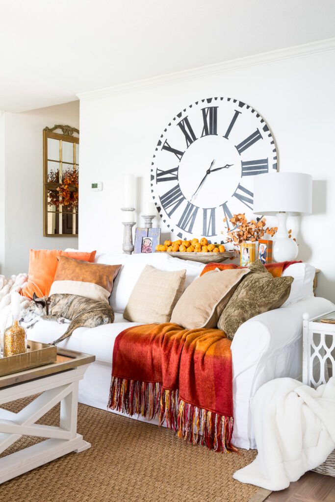 Bloggers Fall home tour living room decorated in fall colors of orange and brown with a navy accent.