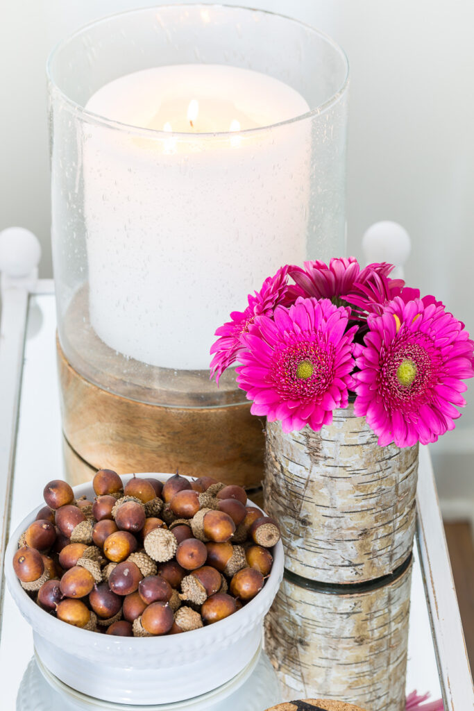 Pretty pink flowers on mirror table with a white candle and a bowlful of acorns.