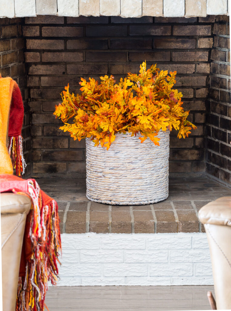 Fall leaves in basket placed in an unused fireplace.