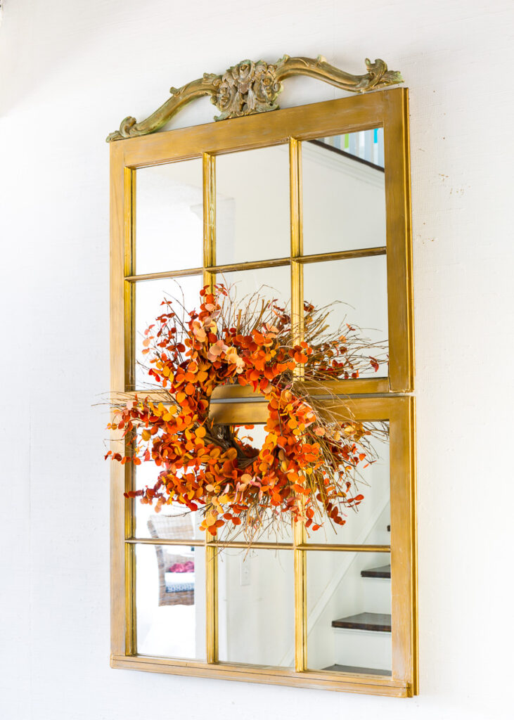 2 window sashes mounted on a wall to create a tall wall mirror. Fall wreath on center.