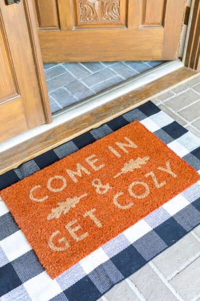 Come In and Get cozy fall doormat on front porch of home