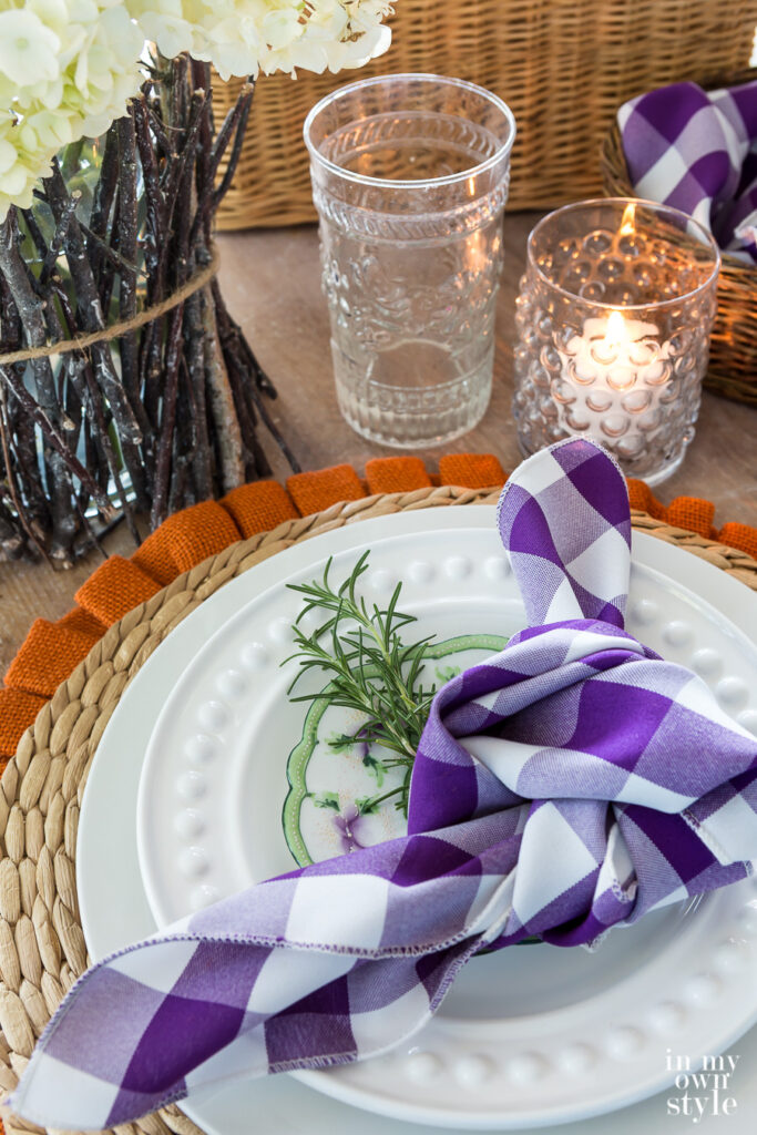 Fall inspired Table setting with purple and white buffalo checked napkin.