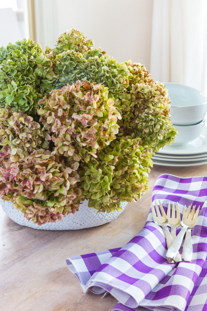 Dried hydrangeas in a white round rattan basket on a kitchen table to create rustic fall decor in a home.