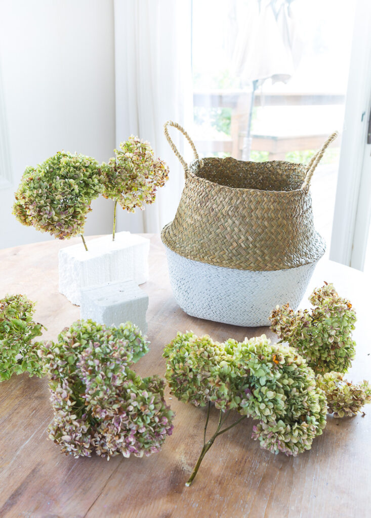Dried hydrangeas and collapsible rattan tote on table getting ready to create a floral arrangement.