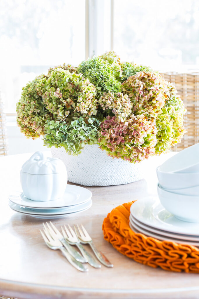 Fall decorating idea using a collapsible rattan tote on a table used as a vase for dried hydrangeas.