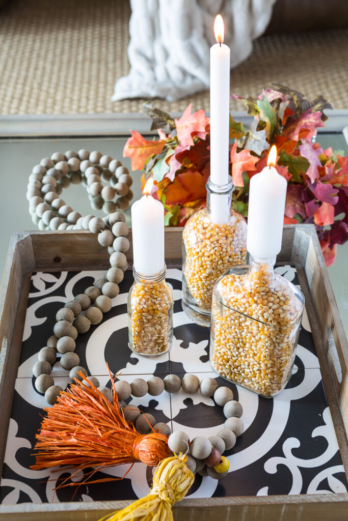 3 popcorn filled clear glass bottles on a table made into autumn inspired candle holders. Creative Fall home decorating.
