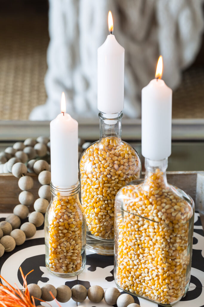 Close up of 3 popcorn filled glass bottle fall candle holders.