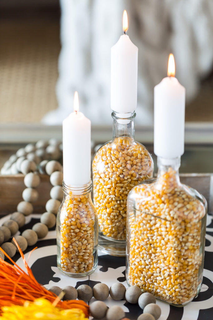 DIY Fall candle holders made from glass food bottle and popcorn kernels