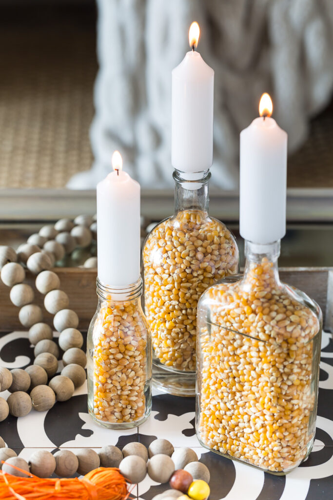 3 glass bottles filled with popcorn and then a candle placed into the bottles opening make for budget friendly fall decor.