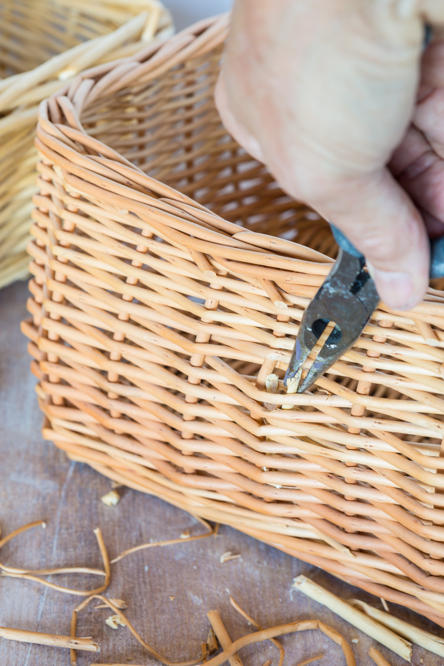 Removing handle and shim reeds on a wicker basket that will be used for cheap, but decorative storage