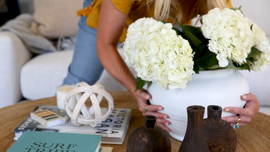 Large white terra cotta vase filled with white hydrangeas from Studio McGee being placed on a coffee table
