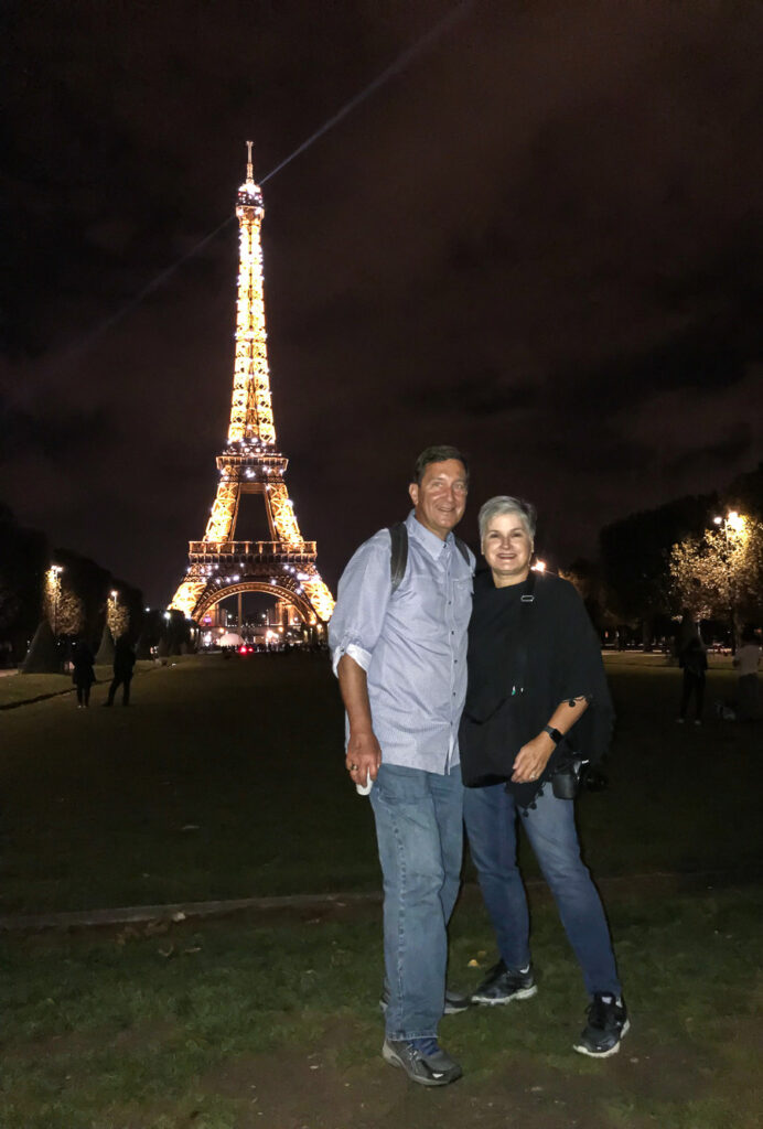 Blogger Diane Henkler and Ed standing in front of the Eiffel Tower at night when it was lit and twinkling. They were on a Paris bike tour at night.