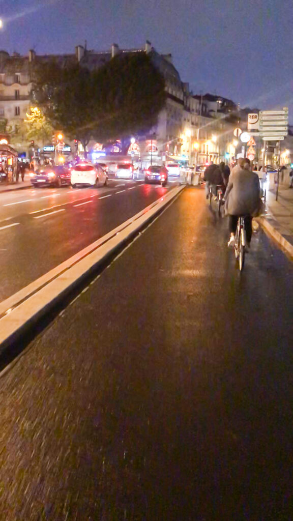 Riding bikes at night in Paris along the bike path in St. Germain.