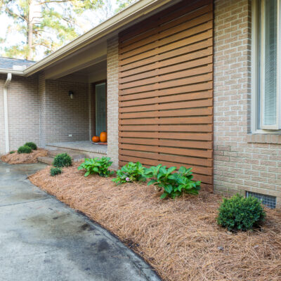 After photo showing stained outdoor modern wood slat accent wall on brick Ranch home.