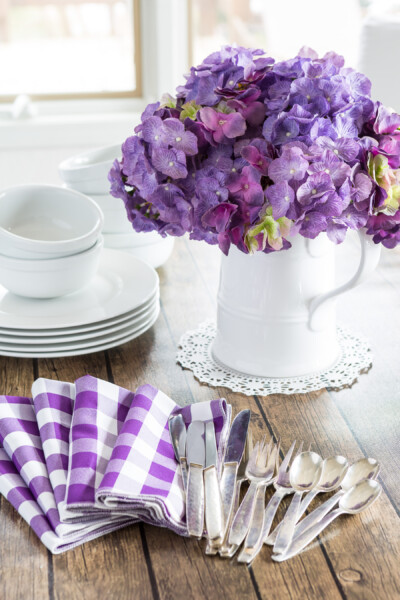 Decorating for spring using White dinnerware and white pitcher filled with purple hydrangeas on a wood table.