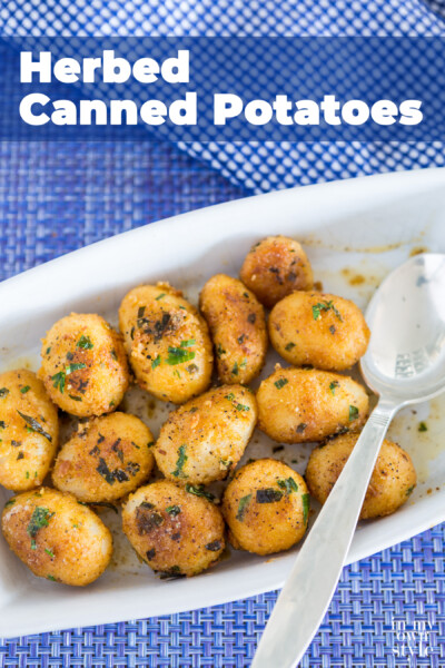 Herbed Encrusted Canned Potatoes in a white serving dishes being spooned out.