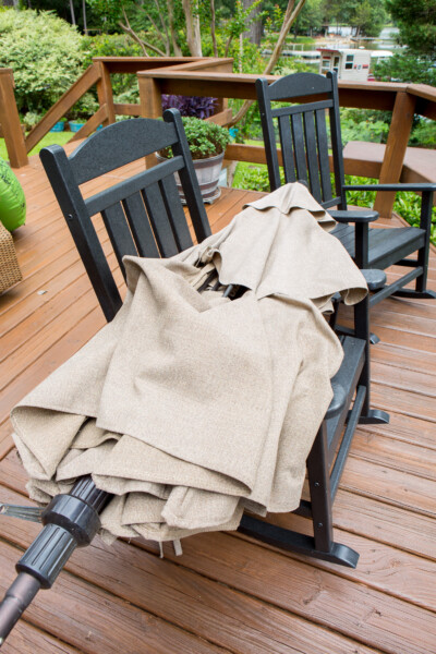 Broken patio umbrella on two deck rocking chairs