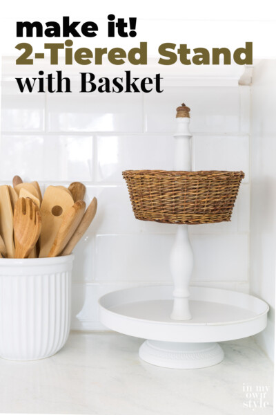 Newly made using parts from other items. White metal 2 tiered stand with a wicker basket and acorn final. text overlay says Make it! 2-Tiered Stand and Wicker Basket