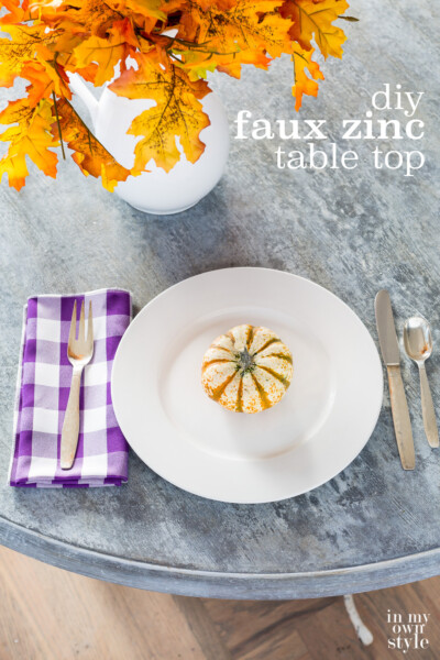 Looking down on faux painted to look like zinc table. Place setting and fall flowers on table. Text overlay sys dit faux zinc table top