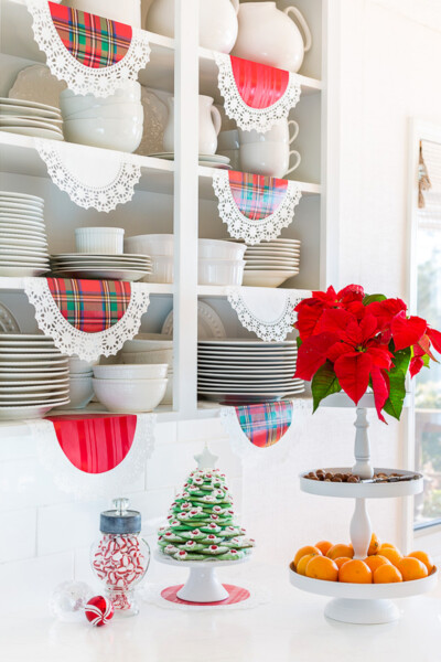 White kitchen with open shelves. Red plaid doilies hanging from the shelves.
