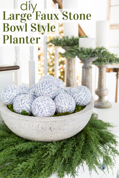 Large faux cement bowl on a wreath on a sideboard. Text overlay says DIY large faux stone bowl style planter.