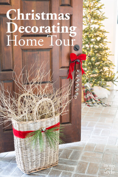 Foyer door open with red ribbon tied sleigh bells and basket. Text overlay says Christmas decorating home tour